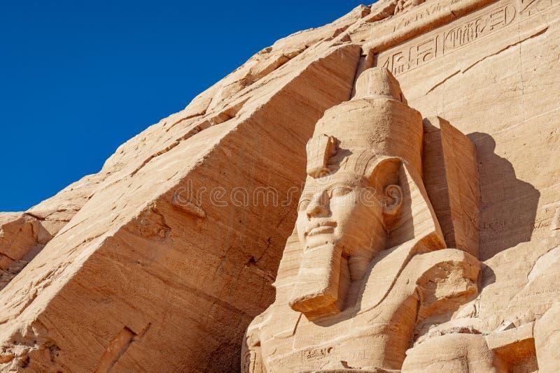 Estátua da rocha de Abu Simbel de Ramesses II no local da herança do UNESCO na vila Egito de Abu Simbel fotos de stock