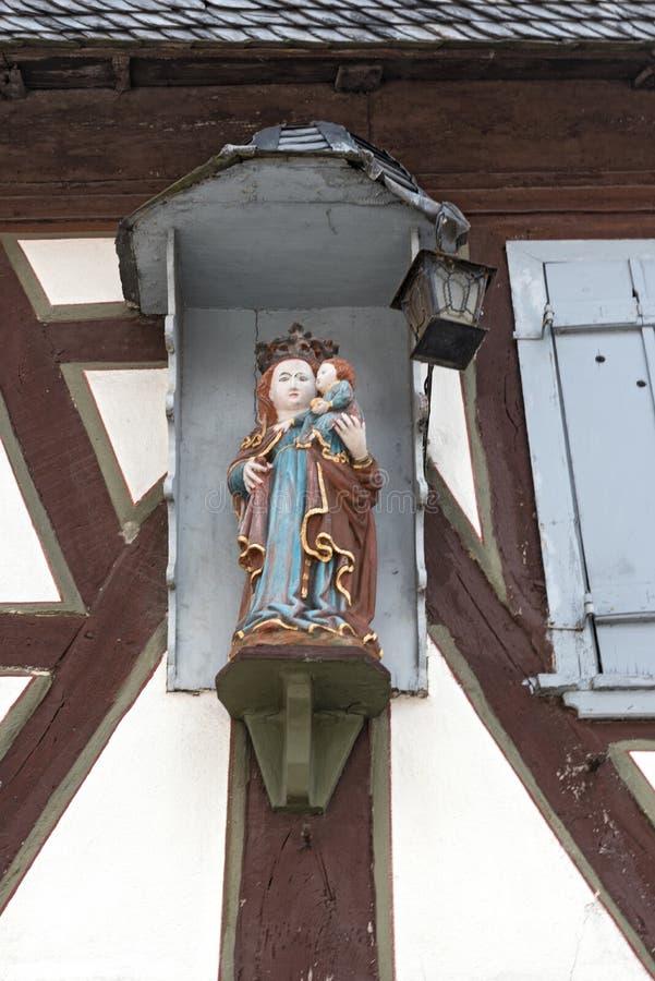A estátua da Virgem Maria e meninos de jesus na parede exterior de uma casa metade-suportada velha fotos de stock