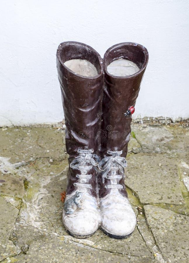 estátua das botas com laços Uma rã e um joaninha estão sentando-se nas botas foto de stock