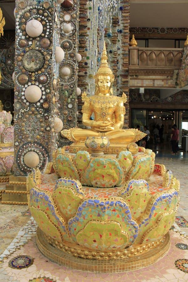 Estátua de assento dourada de Lord Buddha, sentando-se em uns lótus, decorados com as telhas de mosaico bonitas, coloridas na ent imagens de stock