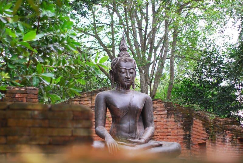 A estátua de bronze antiga da Buda foi criada pela opinião no budismo que existiu desde épocas antigas ao presente imagens de stock