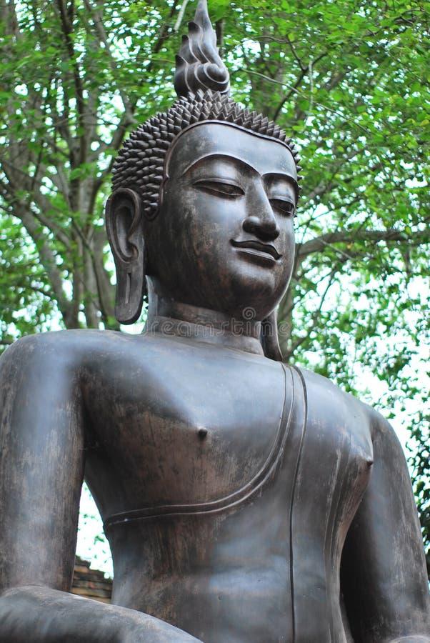 A estátua de bronze antiga da Buda foi criada pela opinião no budismo que existiu desde épocas antigas ao presente fotografia de stock