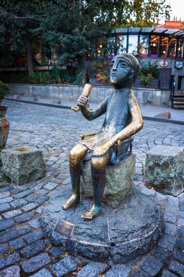 Estátua de bronze de sentar Tamada com o chifre do vinho na rua de Sioni em Tbilisi velho, Geórgia Tamada é um toastmaster Georgi foto de stock royalty free