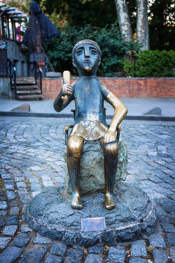 Estátua de bronze de sentar Tamada com o chifre do vinho na rua de Sioni em Tbilisi velho, Geórgia Tamada é um toastmaster Georgi fotografia de stock royalty free