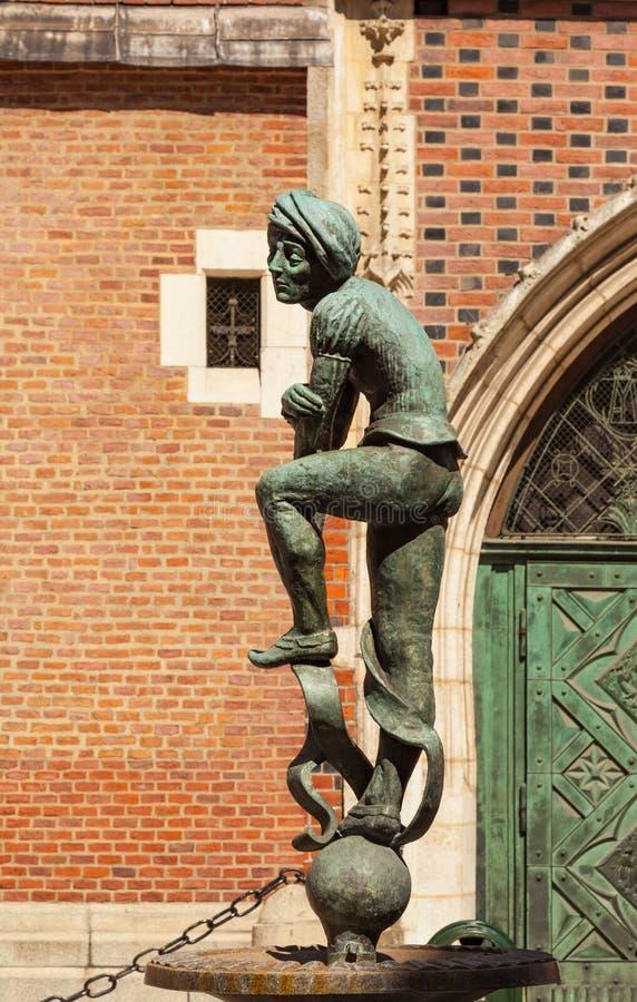 Estátua de bronze de um estudante pobre perto da basílica de St Mary situada em Krakow, Polônia fotografia de stock