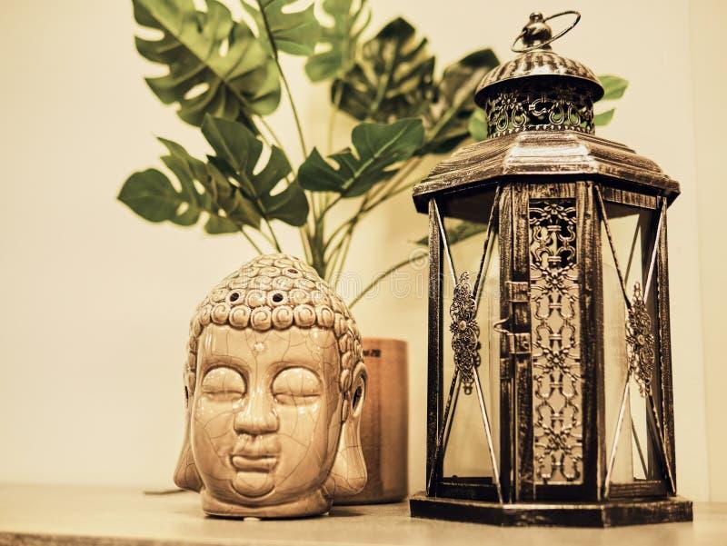 Estátua de Buddah na casa moderna, decoração da casa Estátua principal do isqueiro e da Buda da vela e folhas de Monstera E imagens de stock