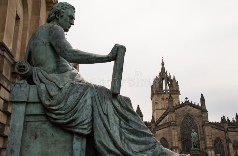 Estátua de David Hume com a catedral no fundo, Edimburgo do ` s do St Gile imagens de stock