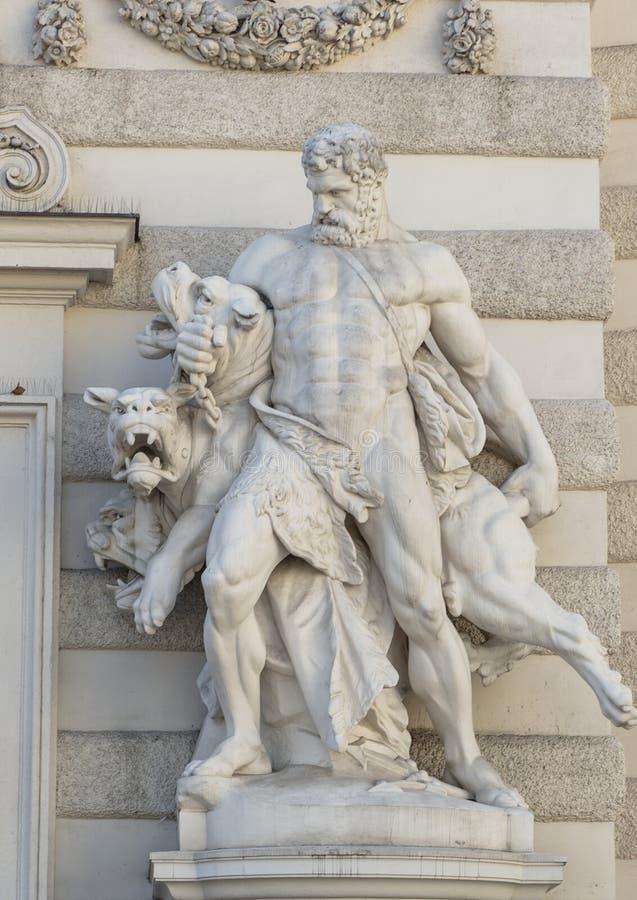 Estátua de Hercules que captura Cerberus na entrada de Michaelerplatz ao Michaelertrakt no palácio de Hofburg, Viena imagens de stock royalty free