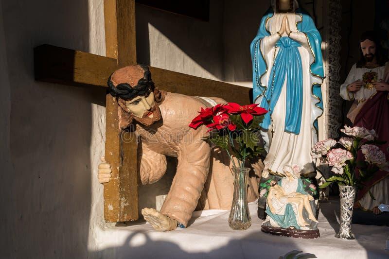 Estátua de Jesus Christ de rastejamento que carrega a cruz e rezar a Virgem Maria de Saint foto de stock