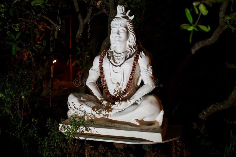 Estátua de mármore branca de Shiva com uma festão das flores em torno de seu pescoço No parque da noite foto de stock