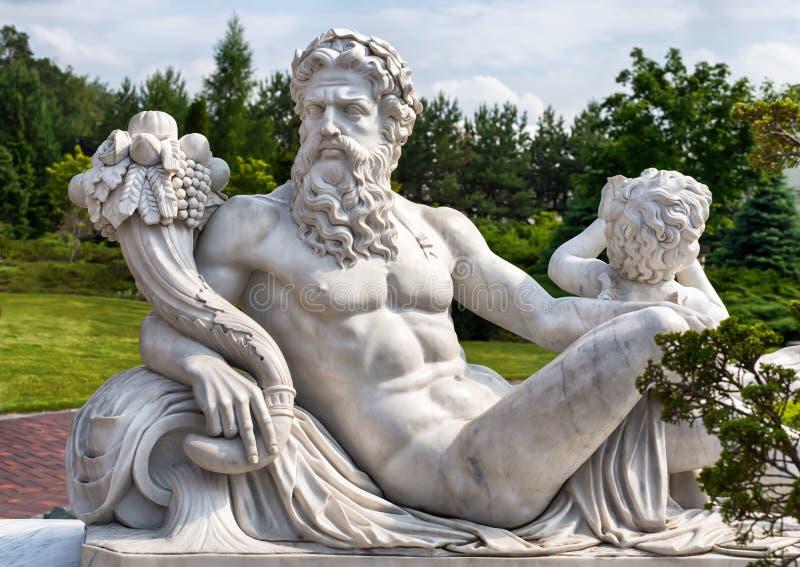 Estátua de mármore do deus olímpico grego com cornucópia em suas mãos imagens de stock