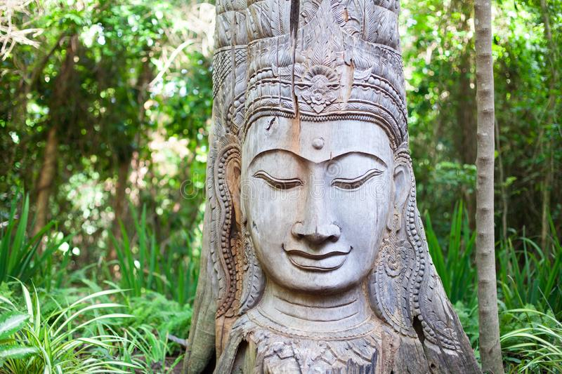Estátua de madeira da Buda no fundo verde das árvores fotografia de stock