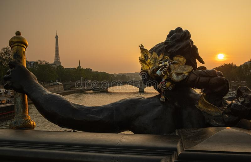 Estátua de Ninfas com fechaduras na ponte de Alexandre III com Torre Eiffel ao fundo à hora do pôr do sol em Paris foto de stock