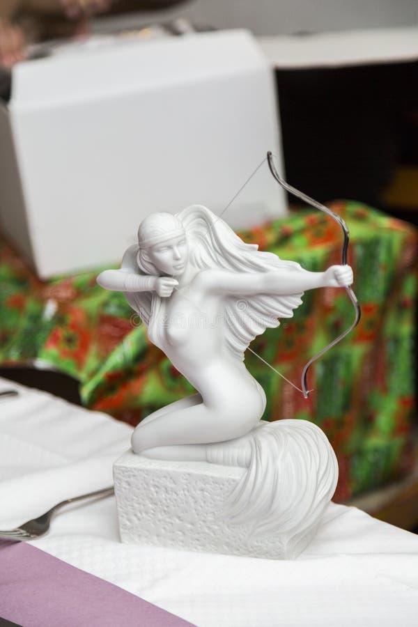 Estátua de pedra branca da mulher despida com curva e setas como um presente fotos de stock royalty free