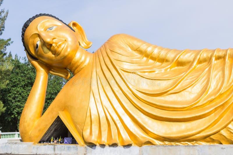 Estátua de reclinação do ouro da Buda em Phuket fotografia de stock royalty free