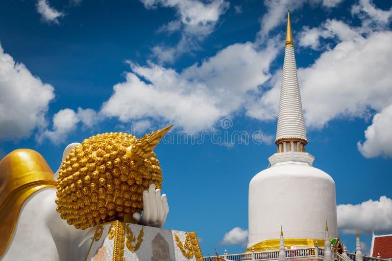 Estátua de reclinação enorme de buddha e pagode santamente no templo budista foto de stock royalty free