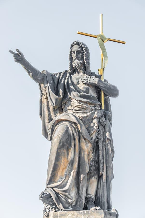 Estátua de Saint com cruz em Charles Bridge em Praga, República Checa, horas de verão fotos de stock royalty free