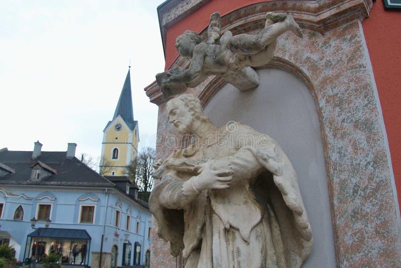 Estátua de Saint John de Nepomuk, e igreja paroquial Áustria fotos de stock
