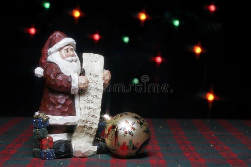 Estátua de Santa com lista e ornamento imagens de stock