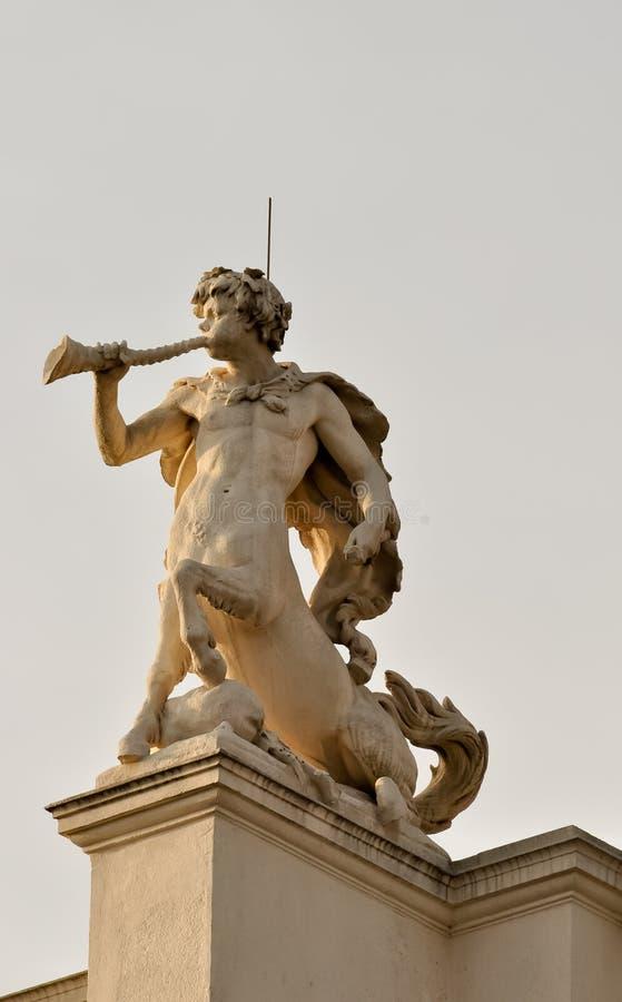 Estátua de um centaur que funde seu chifre foto de stock