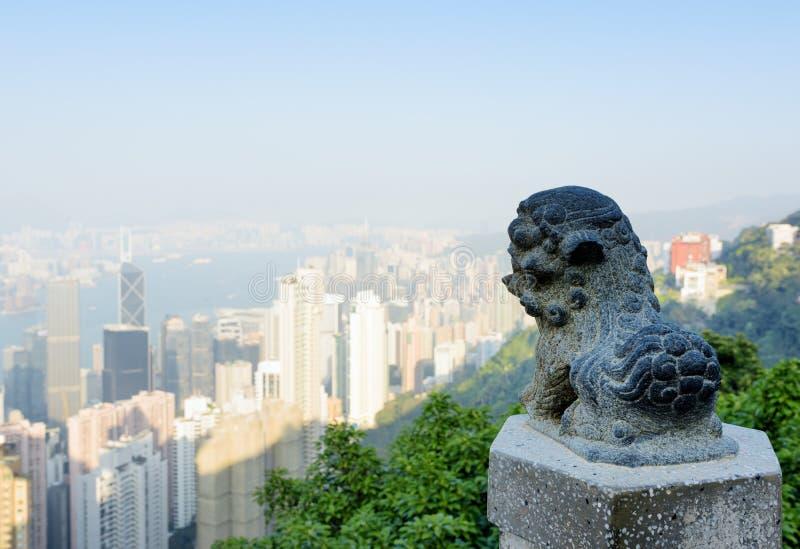 Estátua de um leão em Victoria Peak e na vista da cidade de Hong Kong imagem de stock