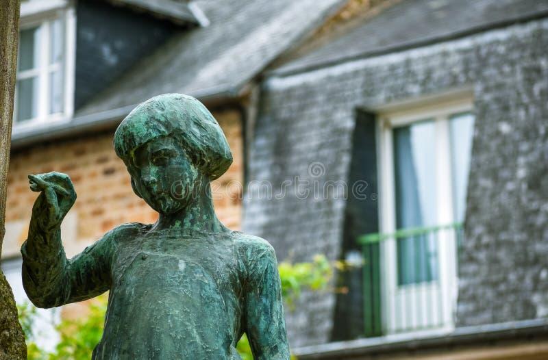 Estátua de uma escrita da menina, com fundo defocused da casa típica do brittany francês imagem de stock