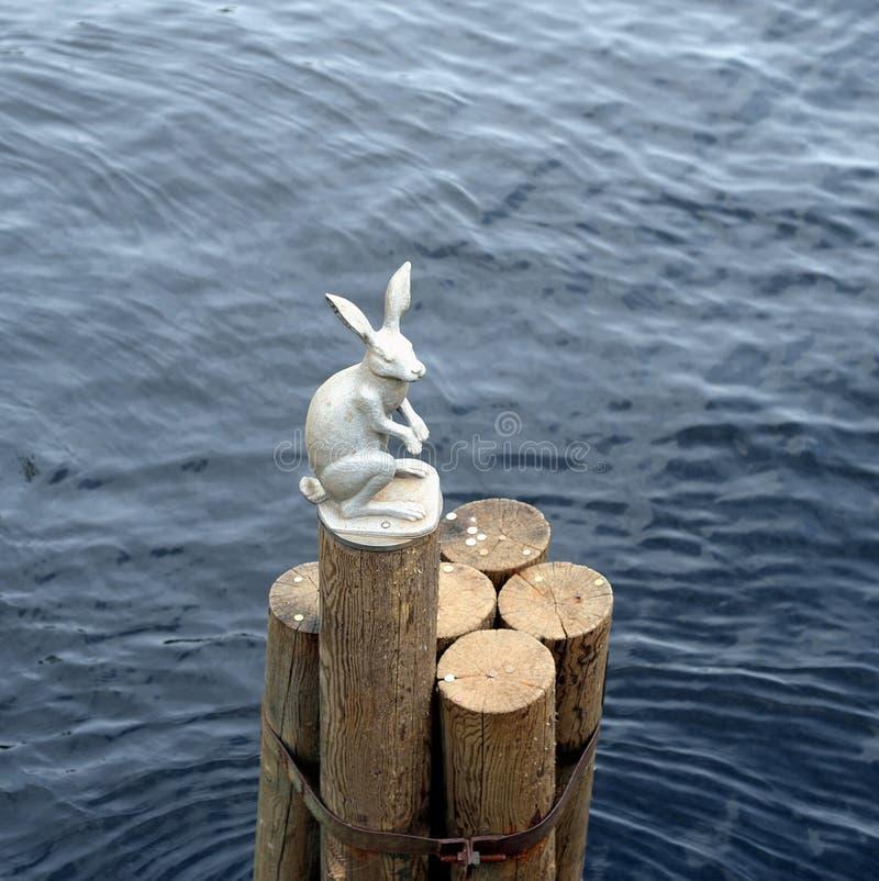 Estátua de uma lebre em um log fotos de stock