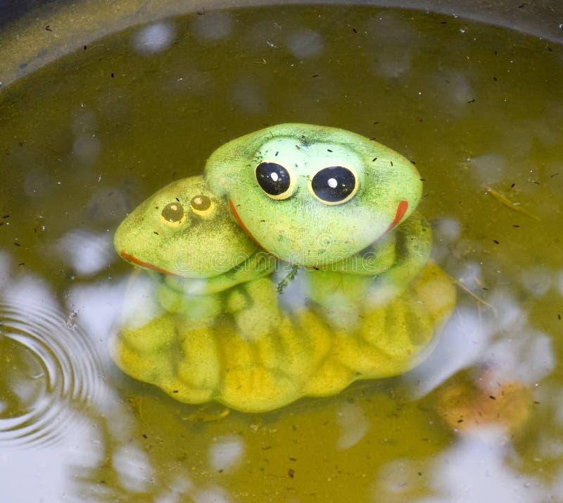 Estátua de uma rã do brinquedo com uma rã subaquática em uma lagoa imagens de stock