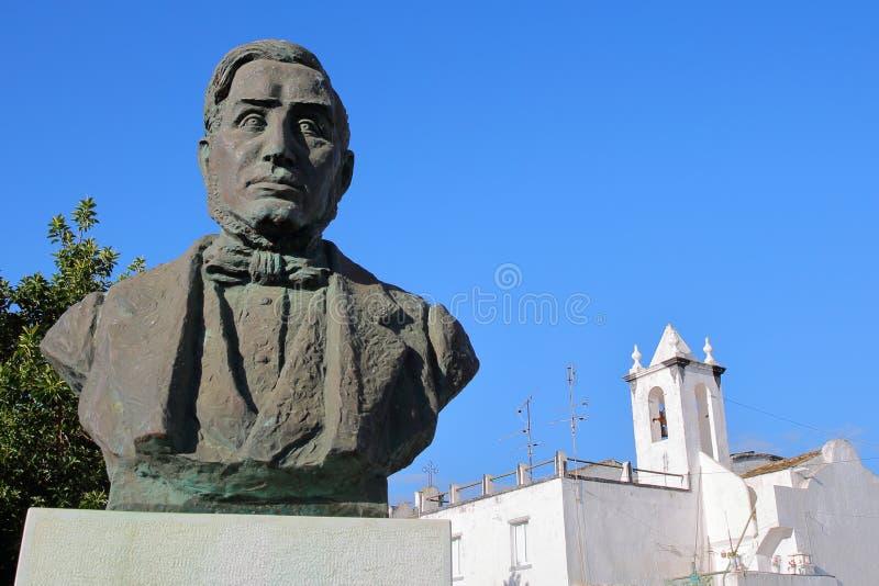 """A estátua do †1803 de Francisco Manuel Alvares Botelho """"1875 com os sutiãs whitewashed do Sao da igreja Católica no fundo fotos de stock"""