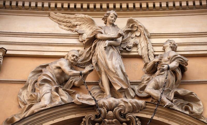 A estátua do anjo aproximadamente para livrar dois escravos juntou-se nos pulsos por uma corrente real do ferro fotos de stock