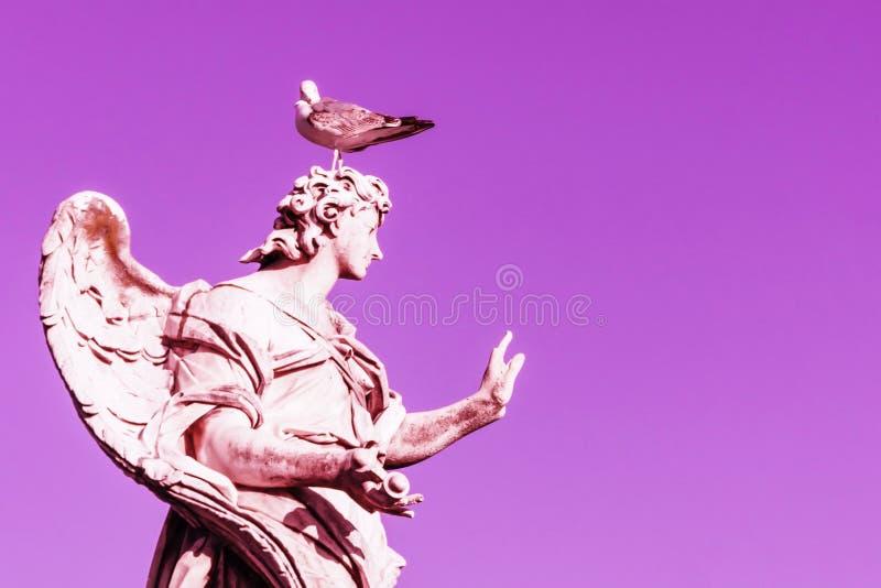 Estátua do anjo com a gaivota na cabeça Céu magenta cor-de-rosa Copie o espaço fotos de stock royalty free