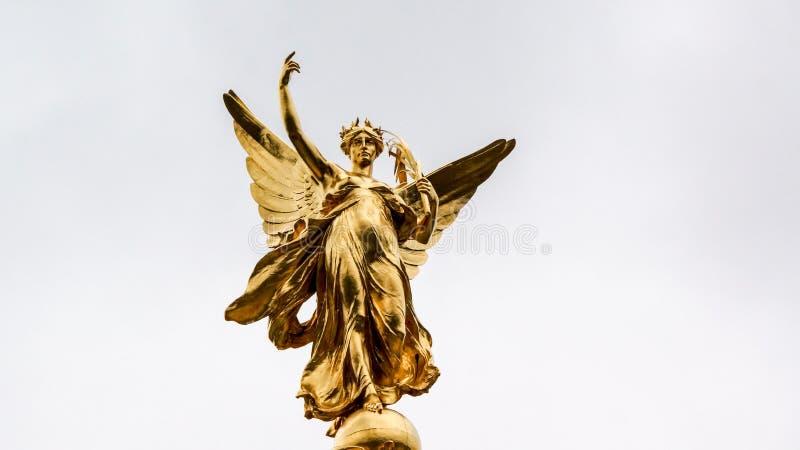 Estátua do anjo do ouro que alcança para o céu imagens de stock