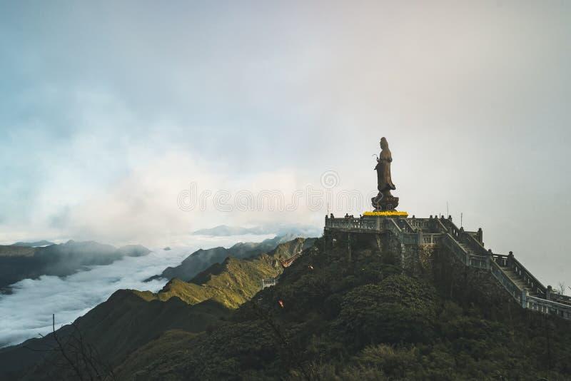 Estátua do Bodhisattva no pico de montanha de Fansipan a montanha a mais alta no céu azul e na nuvem de opinião bonita do context fotografia de stock