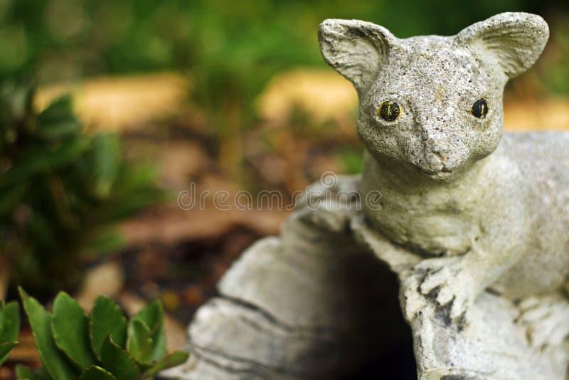 Estátua do gambá no jardim imagens de stock royalty free