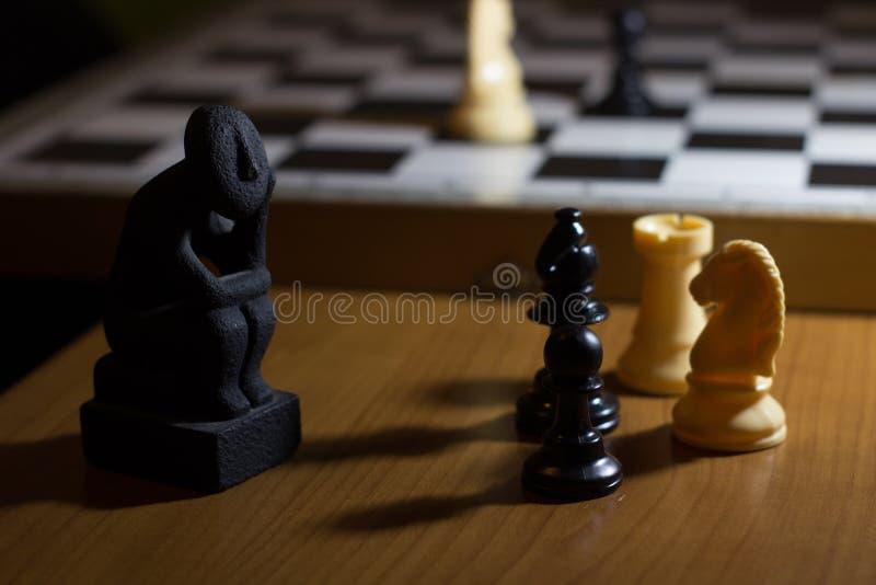 a estátua do pensador em um pensamento pequeno da bobina da placa de xadrez sobre o st foto de stock royalty free