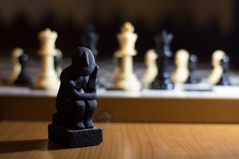 a estátua do pensador em um pensamento pequeno da bobina da placa de xadrez sobre o st imagem de stock