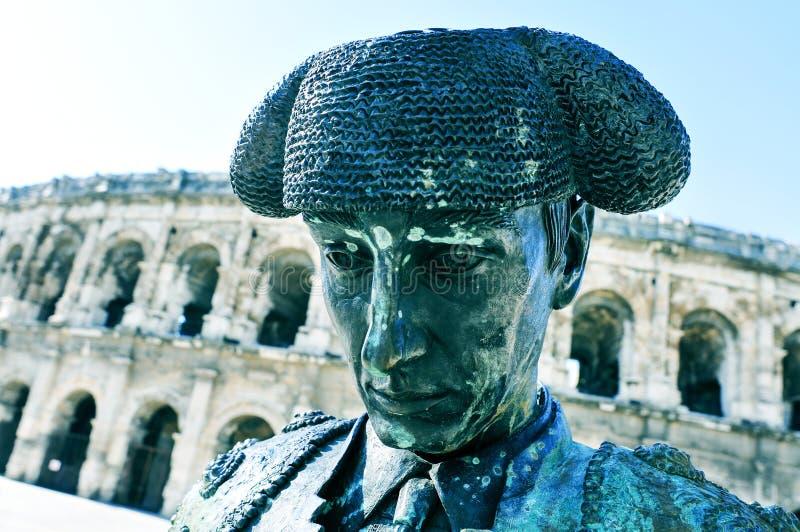 Estátua do toureiro Nimeno II e anfiteatro romano em Nimes, imagem de stock