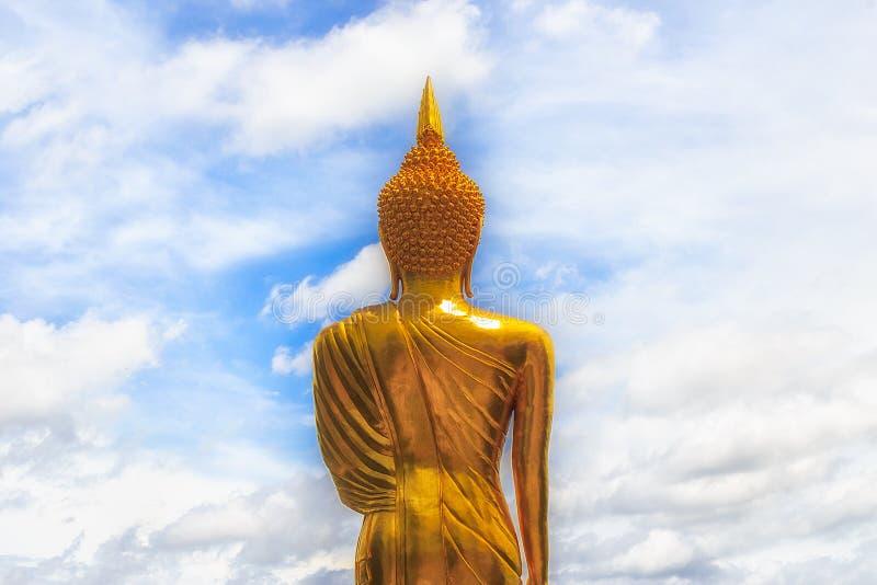 Estátua dourada da Buda e céu azul no templo tailandês imagem de stock