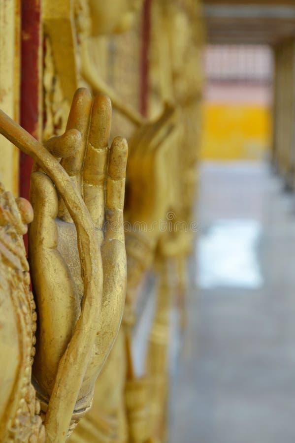 Estátua dourada da mão do anjo que guarda o ramo dos lótus na parede do templo foto de stock