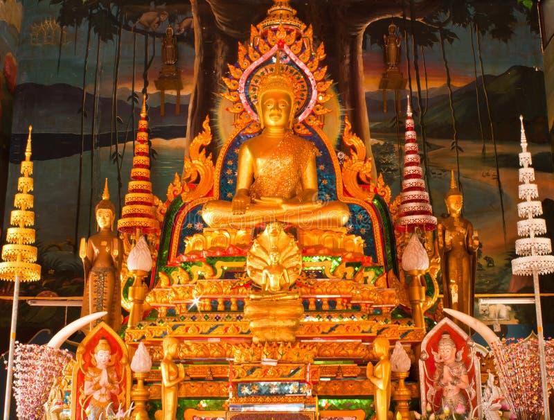 Estátua dourada de buddha dentro de um templo foto de stock