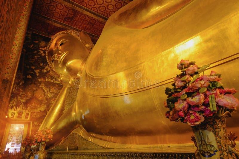 Estátua dourada de reclinação da Buda com arquitetura tailandesa da arte na igreja Wat Pho foto de stock