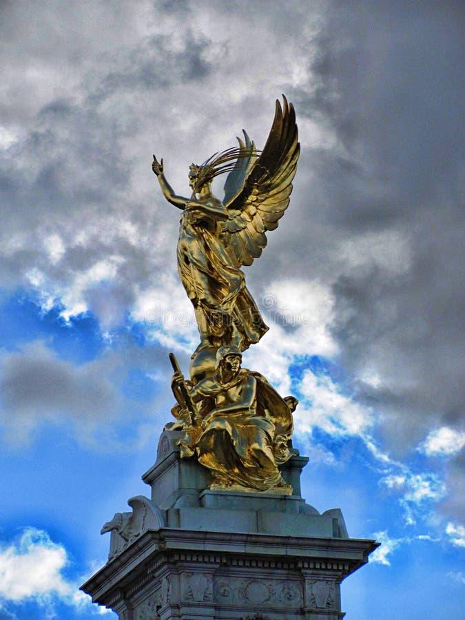 Estátua dourada do anjo com o céu azul nebuloso imagem de stock
