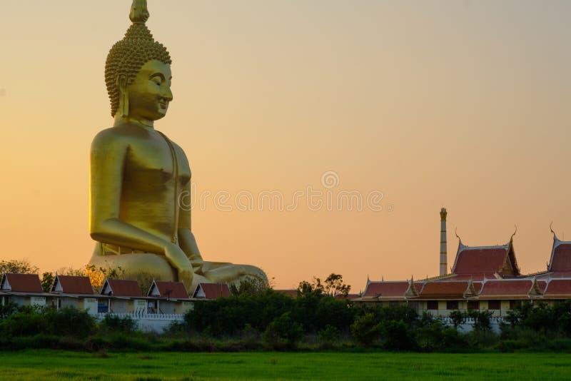 A estátua dourada a mais grande da Buda no campo verde em Tailândia em imagens de stock