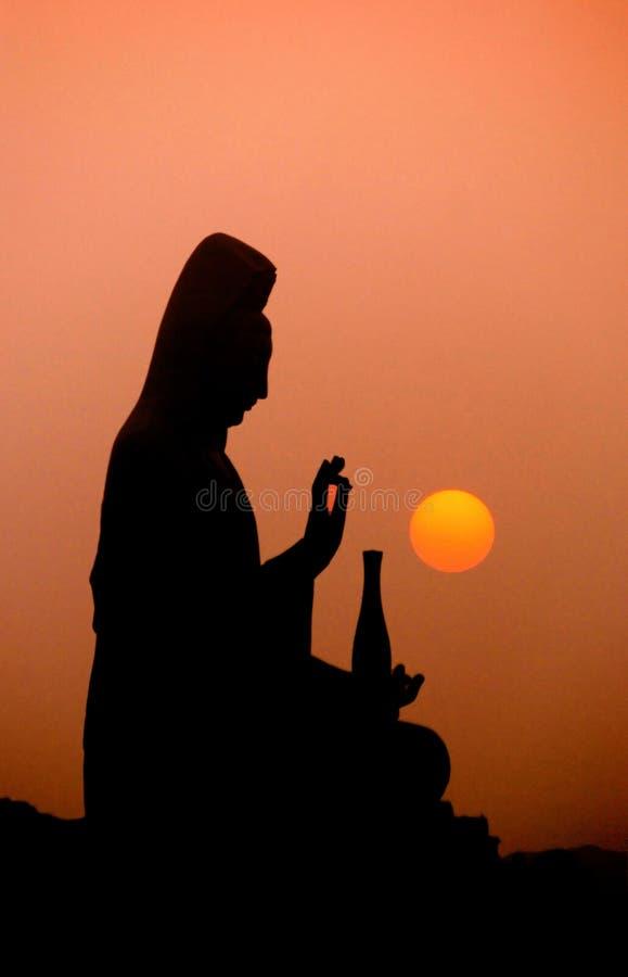 A estátua e o por do sol de Kwan-yin fotos de stock royalty free