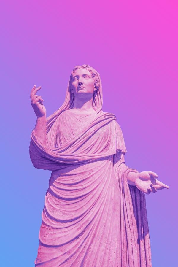 Estátua fêmea no rosa corajoso e em cores de néon azuis no fundo do inclinação fotos de stock