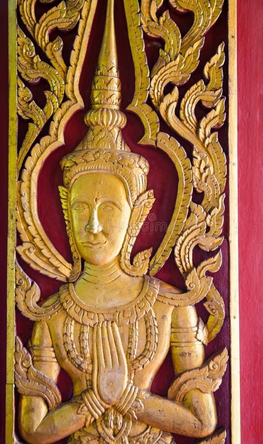 Estátua feericamente de madeira na porta da igreja imagem de stock