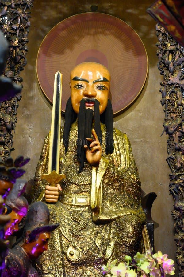 Estátua feroz com espada e casaco dourado no templo budista asiático Jade Emperor Pagoda, Cidade de Ho-Chi-Minh, Vietname fotos de stock royalty free