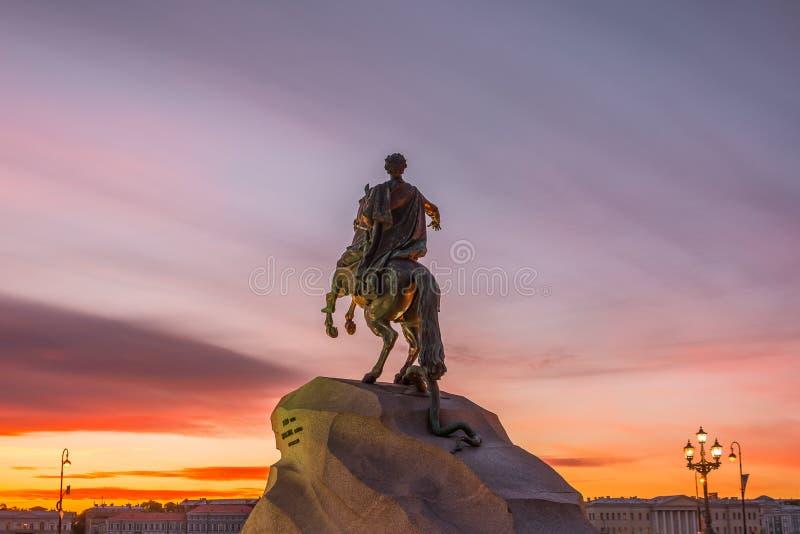 Estátua histórica do monumento a Peter 1, cavaleiro de bronze em St Petersburg no céu da noite do por do sol foto de stock
