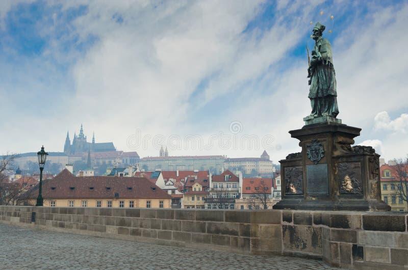Estátua na ponte de Charles, opinião do castelo de Praga imagens de stock
