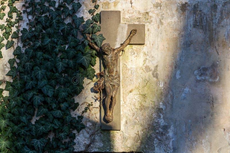 Estátua oxidada bonita da crucificação de Jesus Christ durante o por do sol coberto em parte com a hera comum, hélice de hedera n foto de stock royalty free